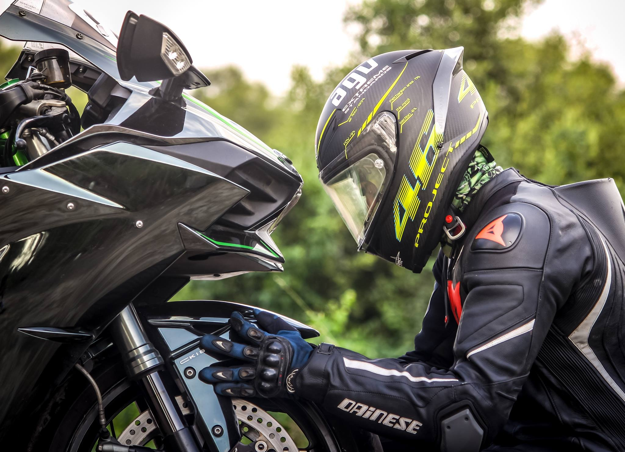 Un motard avec un casque devant une moto noire