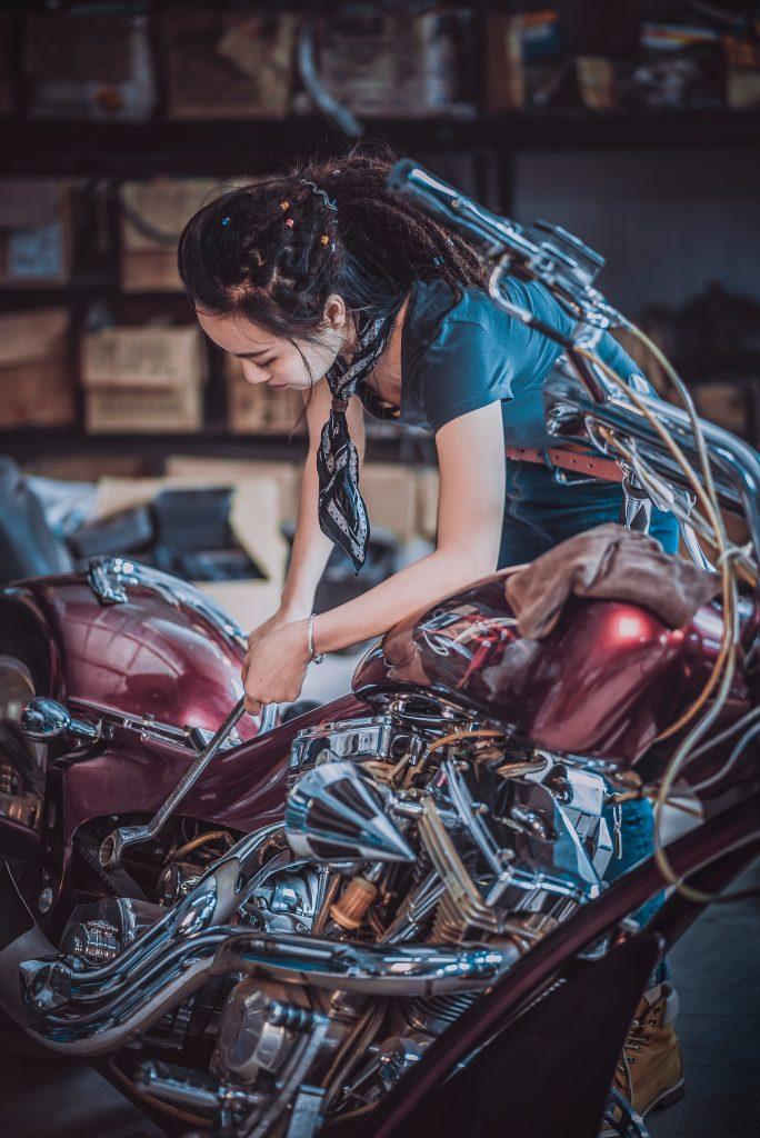 Un femme réparant une moto dans un garage